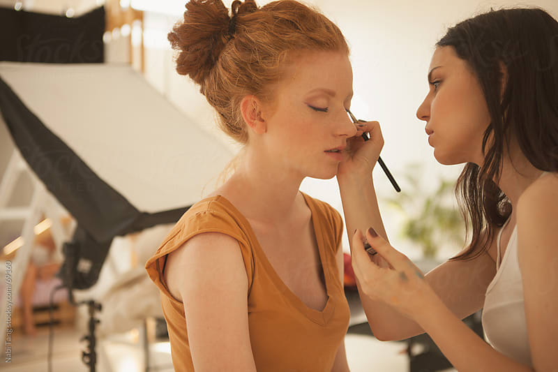 Make-up Artist applying make up on model in the photography studio by Nabi Tang for Stocksy United