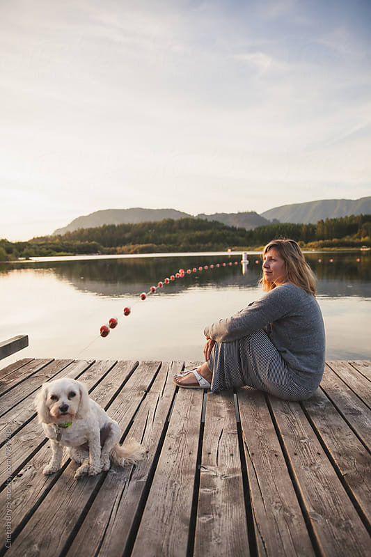 Sitting at the edge of the dock. by Cherish Bryck for Stocksy United