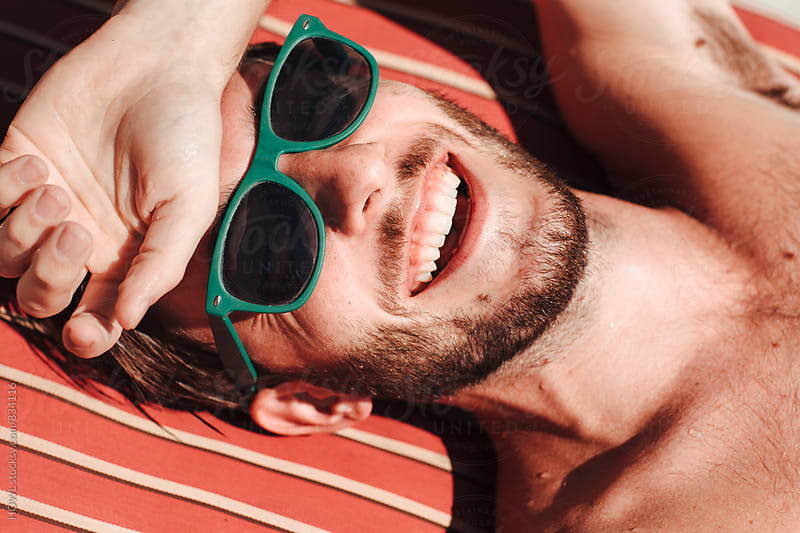 A bearded man in sunglasses relaxes in the sun in Malibu by HOWL for Stocksy United