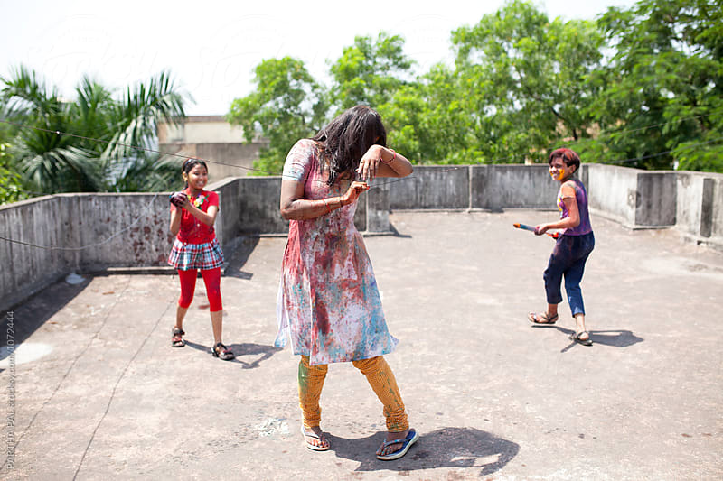 Teenage girl plying Holi with and adult woman by PARTHA PAL for Stocksy United
