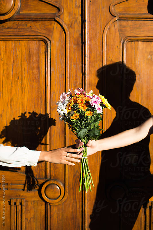A guy giving to his girlfriend a bouquet of flowers by michela ravasio for Stocksy United
