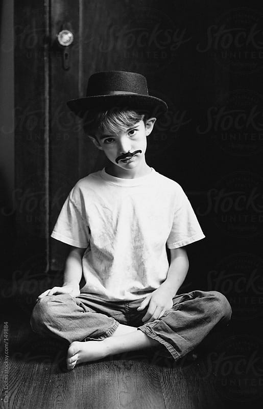 Boy wearing vintage hat and fake mustache by Cara Dolan for Stocksy United