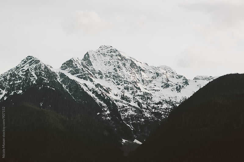 snowy mountains on cloudy day by Nicole Mason for Stocksy United