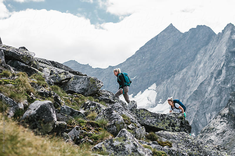 two female hiking friends hiking up a mountain by Leander Nardin for Stocksy United