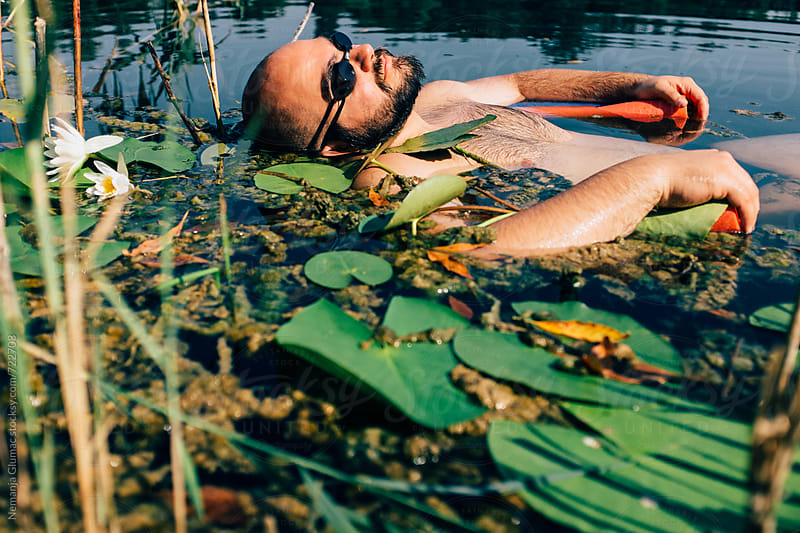 Man Floating Among Freshwater Weed and Reed by Nemanja Glumac for Stocksy United