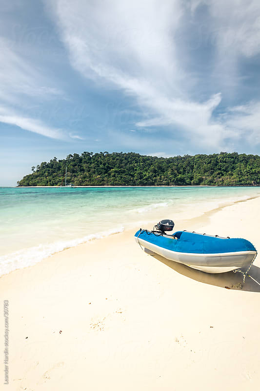 small boat on a lonesome beach by Leander Nardin for Stocksy United