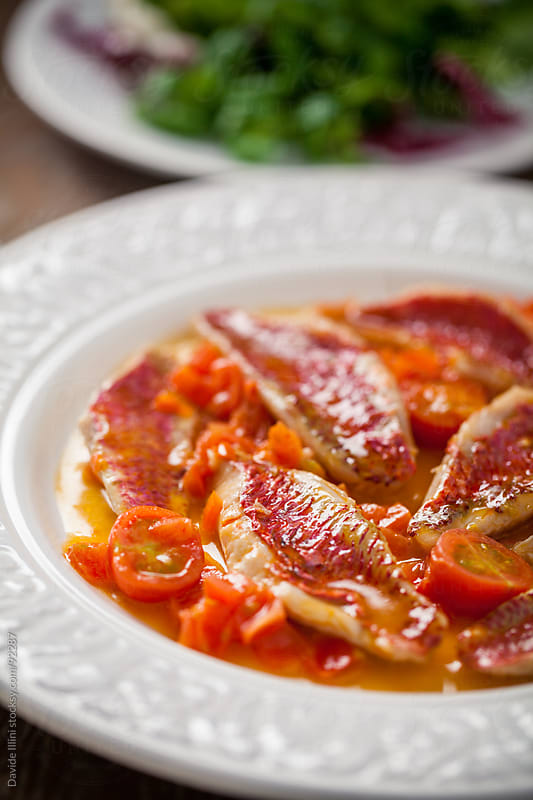Red mullet with fresh cherry tomatoes by Davide Illini for Stocksy United