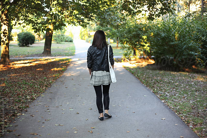 Stylish woman walking through the park during an autumn day  by VeaVea for Stocksy United