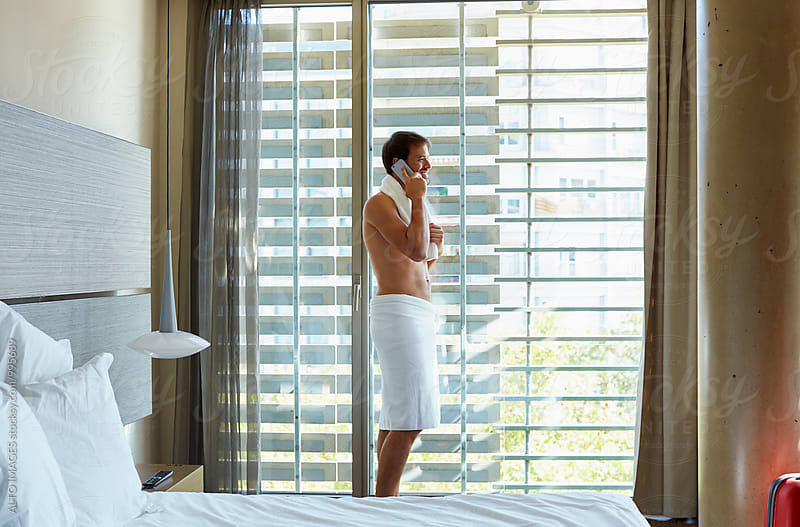 Man Talking On Mobile Phone In Hotel Room by ALTO IMAGES for Stocksy United