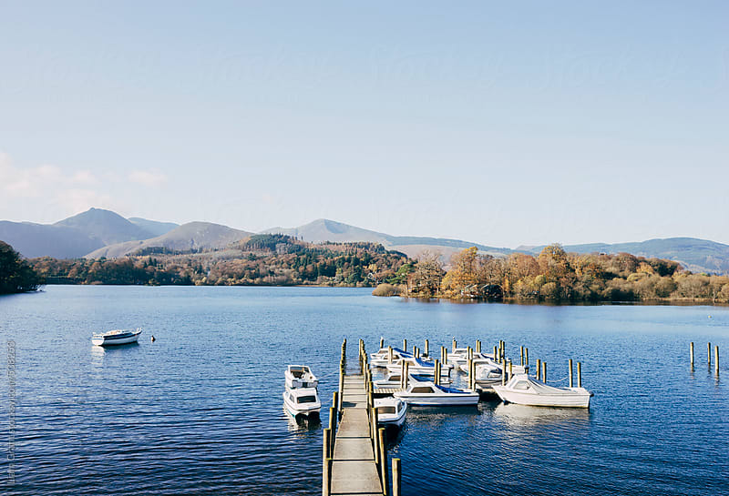 Day boats moored at a jetty on Derwent Water. by Liam Grant for Stocksy United