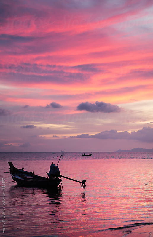 Silhouette of fishing boat in sea with purple sunset in background by Audrey Shtecinjo for Stocksy United