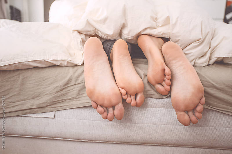 Feet of a couple relaxing on the bed. by BONNINSTUDIO for Stocksy United