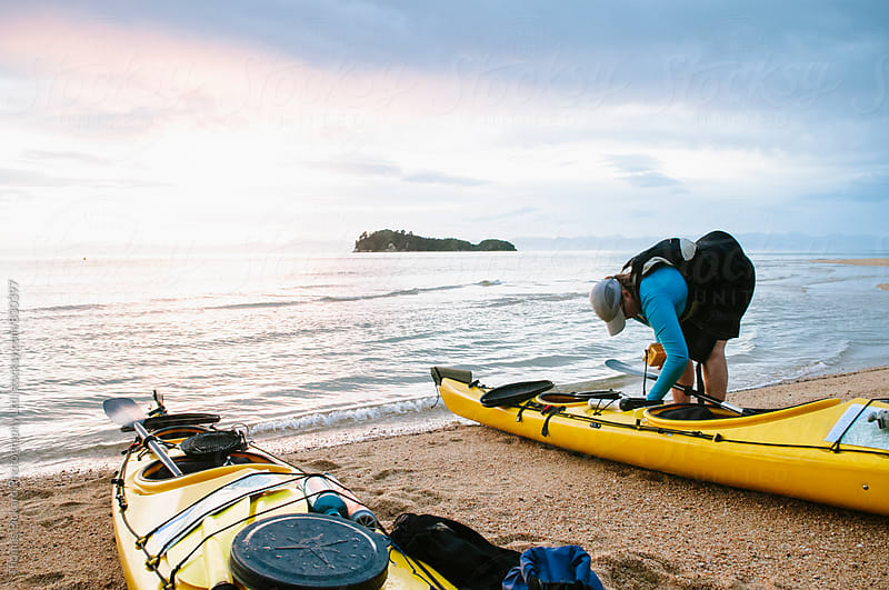 Woman packing her sea kayak, Abel Tasman National Park, New Zealand. by Thomas Pickard for Stocksy United