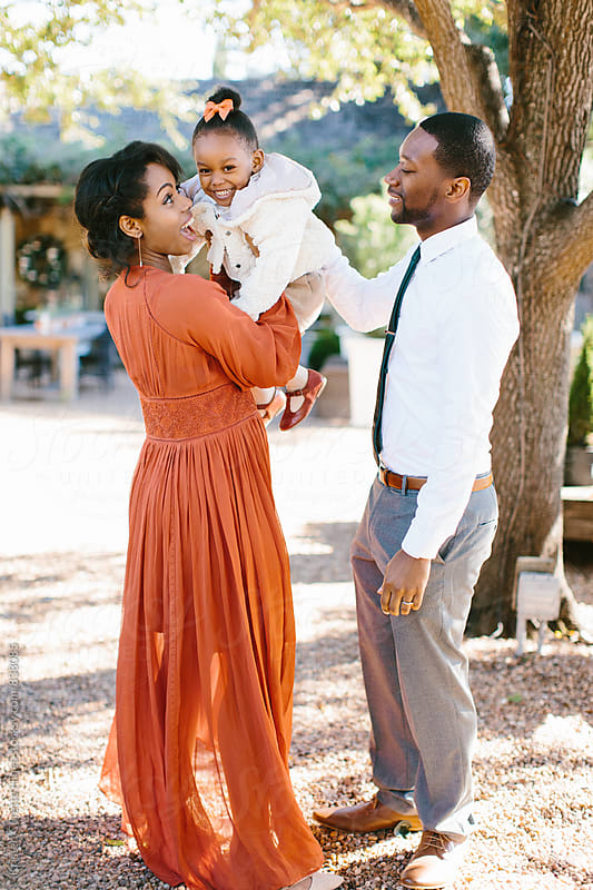 Portrait of a beautiful African American family playing with their little girl in the park  by Kristen Curette Hines for Stocksy United