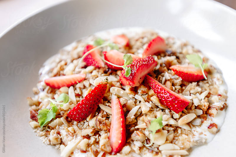 healthy breakfast of granola, strawberries and yoghurt by Gillian Vann for Stocksy United
