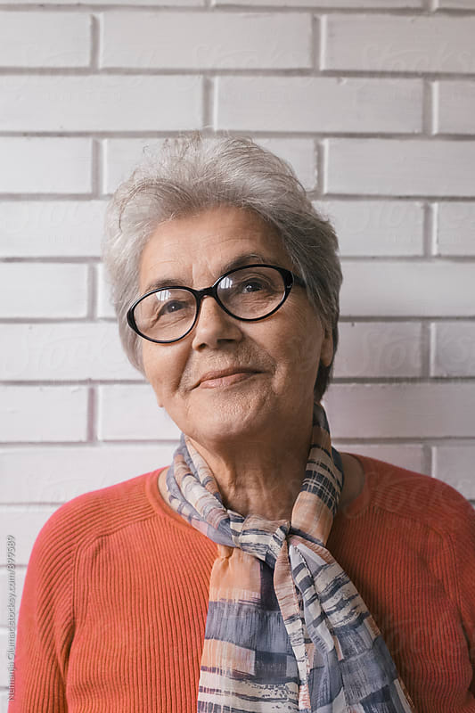 Beautiful senior woman in her seventies with short grey hair and glasses.  by Nemanja Glumac for Stocksy United