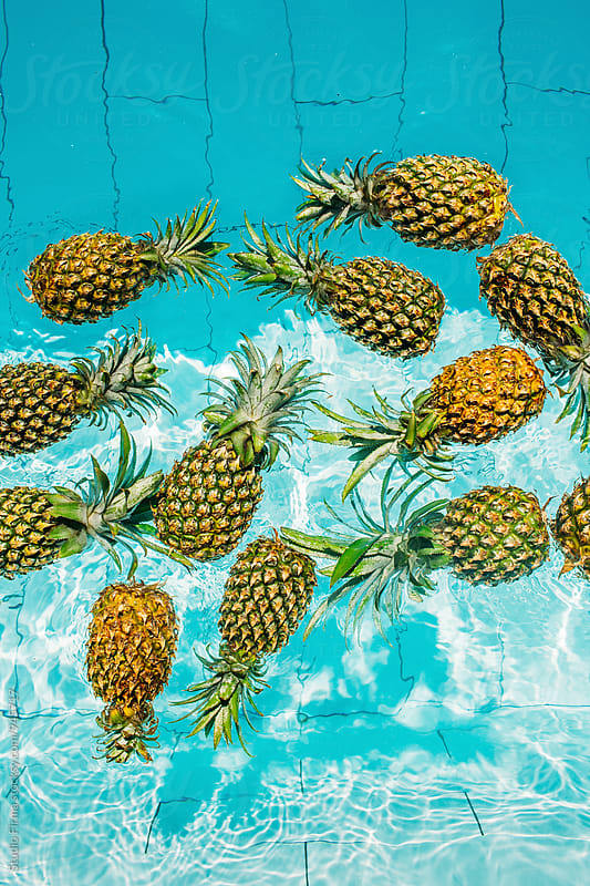 Pineapples in a swimming pool. by Studio Firma for Stocksy United