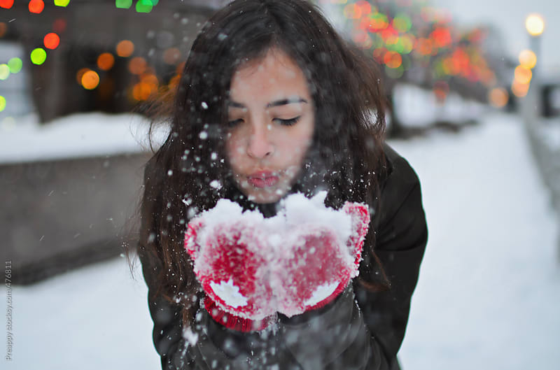 Teen girl blowing a handful of snow by Preappy for Stocksy United