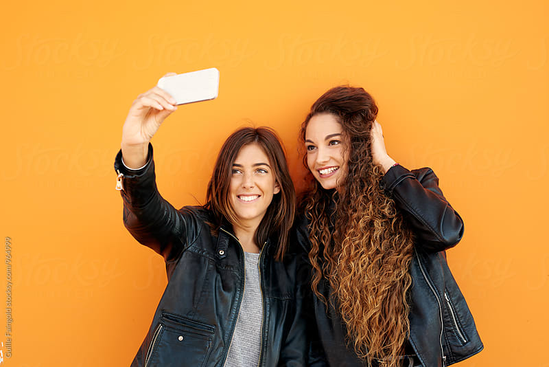 Smiling girls making selfie with cell phone by Guille Faingold for Stocksy United