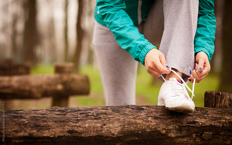 Young blond woman tying a shoe lace before jogging. by Mosuno for Stocksy United