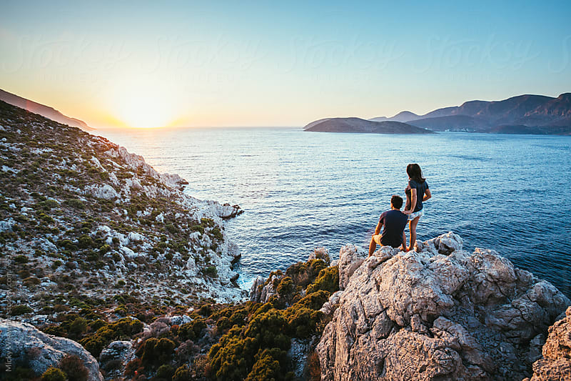 Outdoor couple on a rocky outcrop overlooking an expansive sea view at sunset by Micky Wiswedel for Stocksy United