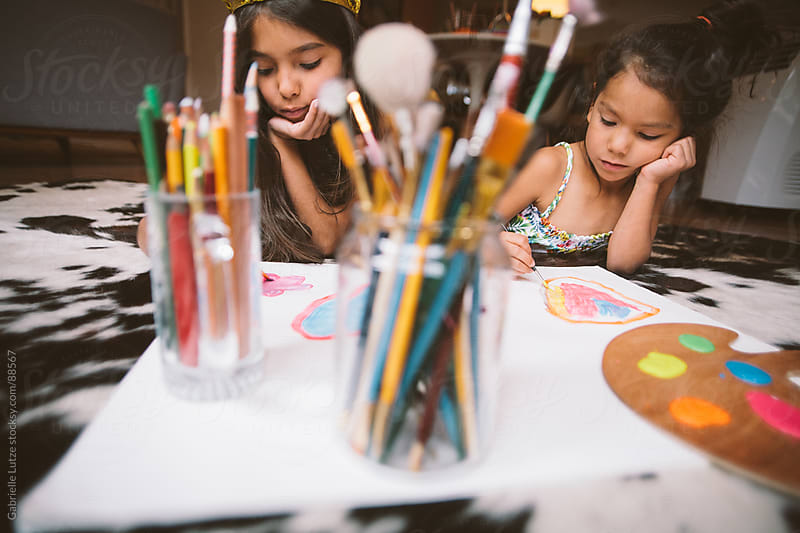 Sisters Painting Together by Gabrielle Lutze for Stocksy United