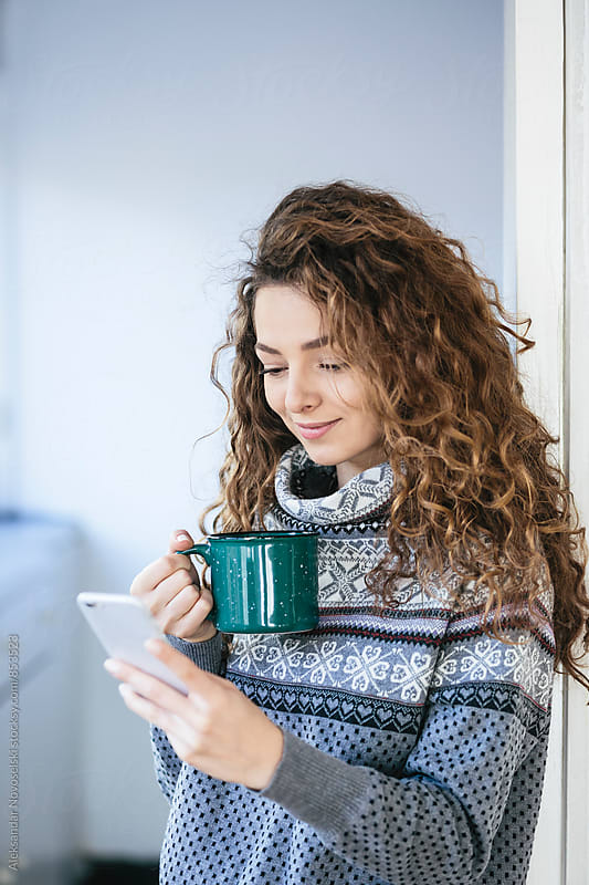 Beautiful woman with curly hair drinking tea and using her smartphone at home by Aleksandar Novoselski for Stocksy United