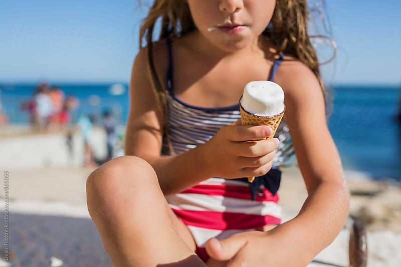 Child eating ice cream on beach. by Dejan Ristovski for Stocksy United