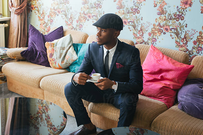 Elegant Young Black Man Sitting in Stylish Living Room and Drinking Espresso by Julien L. Balmer for Stocksy United