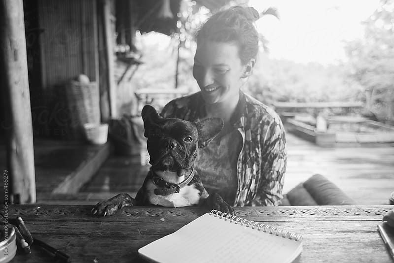 Black and white portrait of a smiling woman and a cute french bull dog by Jovo Jovanovic for Stocksy United