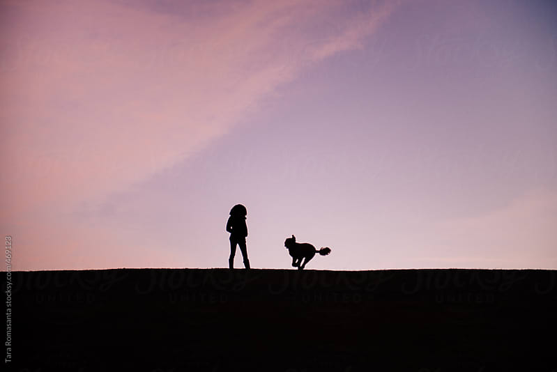 silhouette of a woman, dog running toward her by Tara Romasanta for Stocksy United