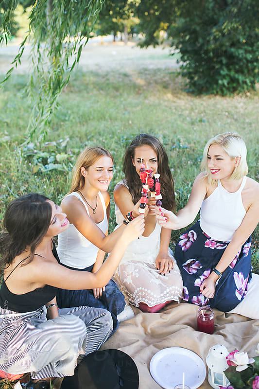 Happy female friends on a picnic in nature by Jovana Rikalo for Stocksy United