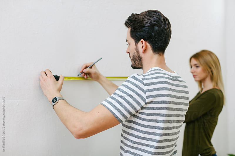 Young couple measuring the wall to hanging a picture.  by BONNINSTUDIO for Stocksy United