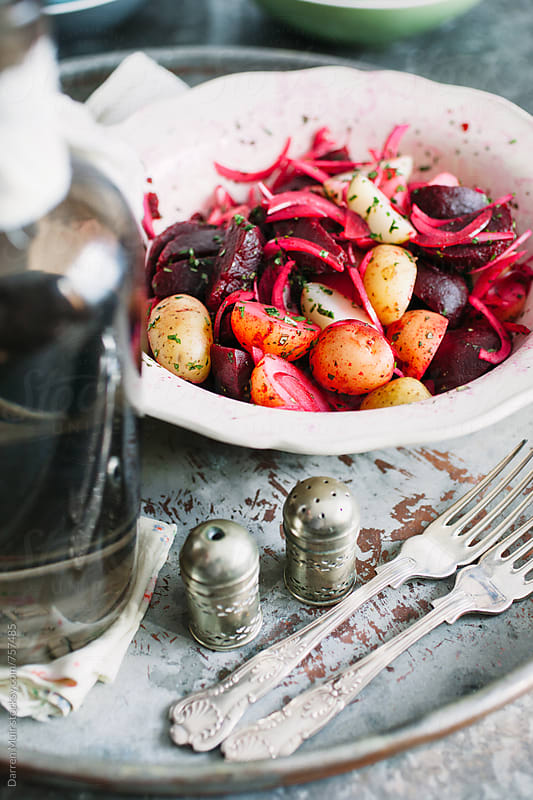 Beet salad in a white serving bowl on a metal tray. by Darren Muir for Stocksy United