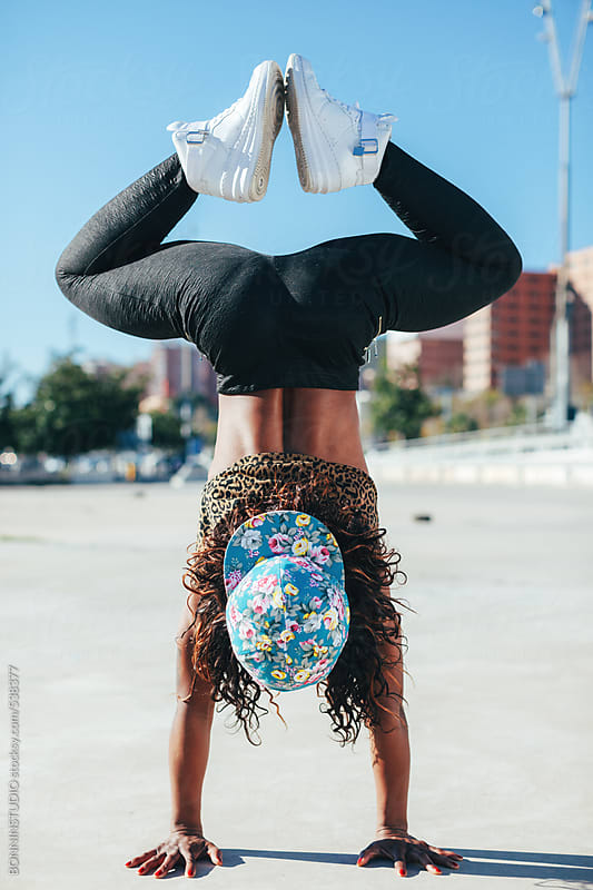 Young african american woman performing break dance in a city. by BONNINSTUDIO for Stocksy United