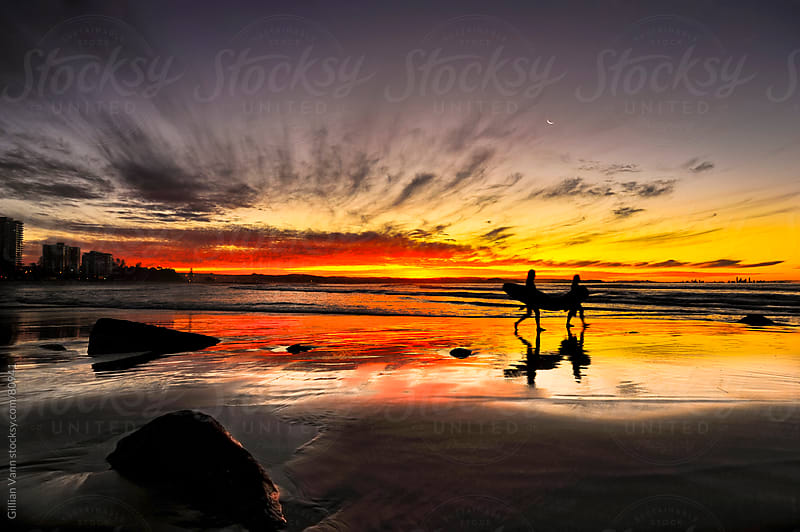 surfers head home as the sun sets by Gillian Vann for Stocksy United