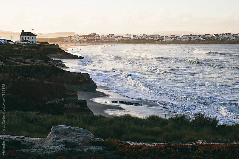 View of the coast at sunset with waves and small houses in the background by Alejandro Moreno de Carlos for Stocksy United