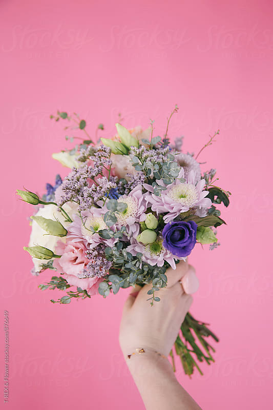 Hand holding beautiful bridal bouquet against pink background by T-REX & Flower for Stocksy United