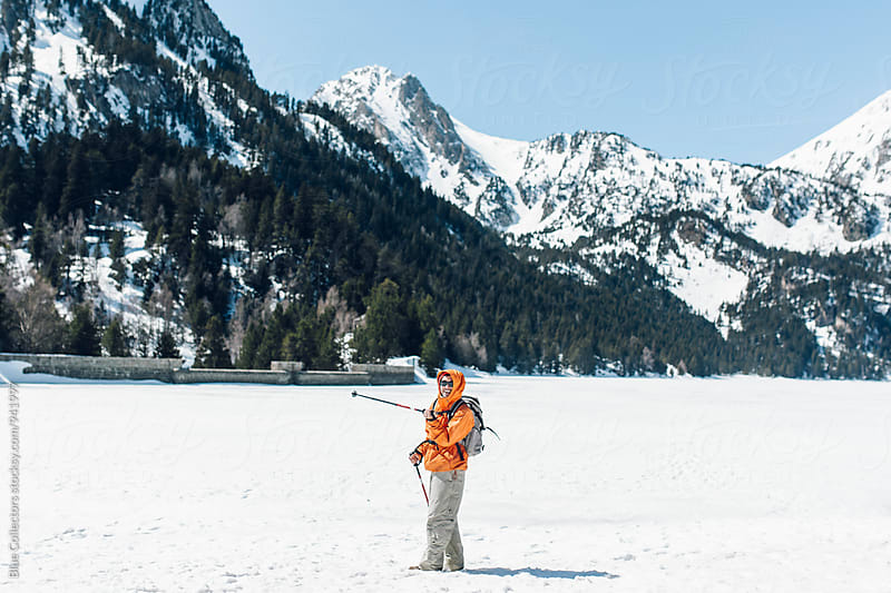 View of a mountaineer on the snowy lake smilingly and looking the landscape.. by Jordi Rulló for Stocksy United