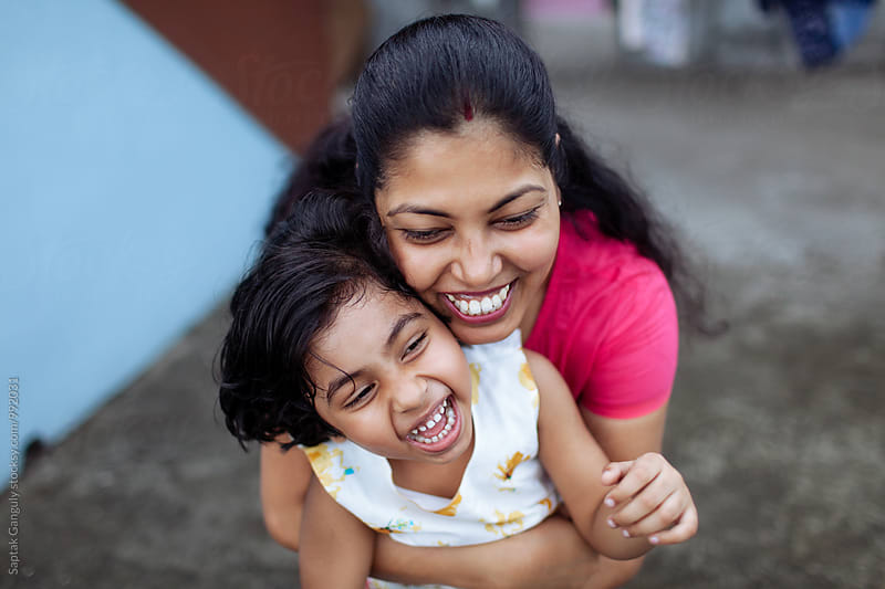 Mother hugging her daughter from behind,happy family by Saptak Ganguly for Stocksy United