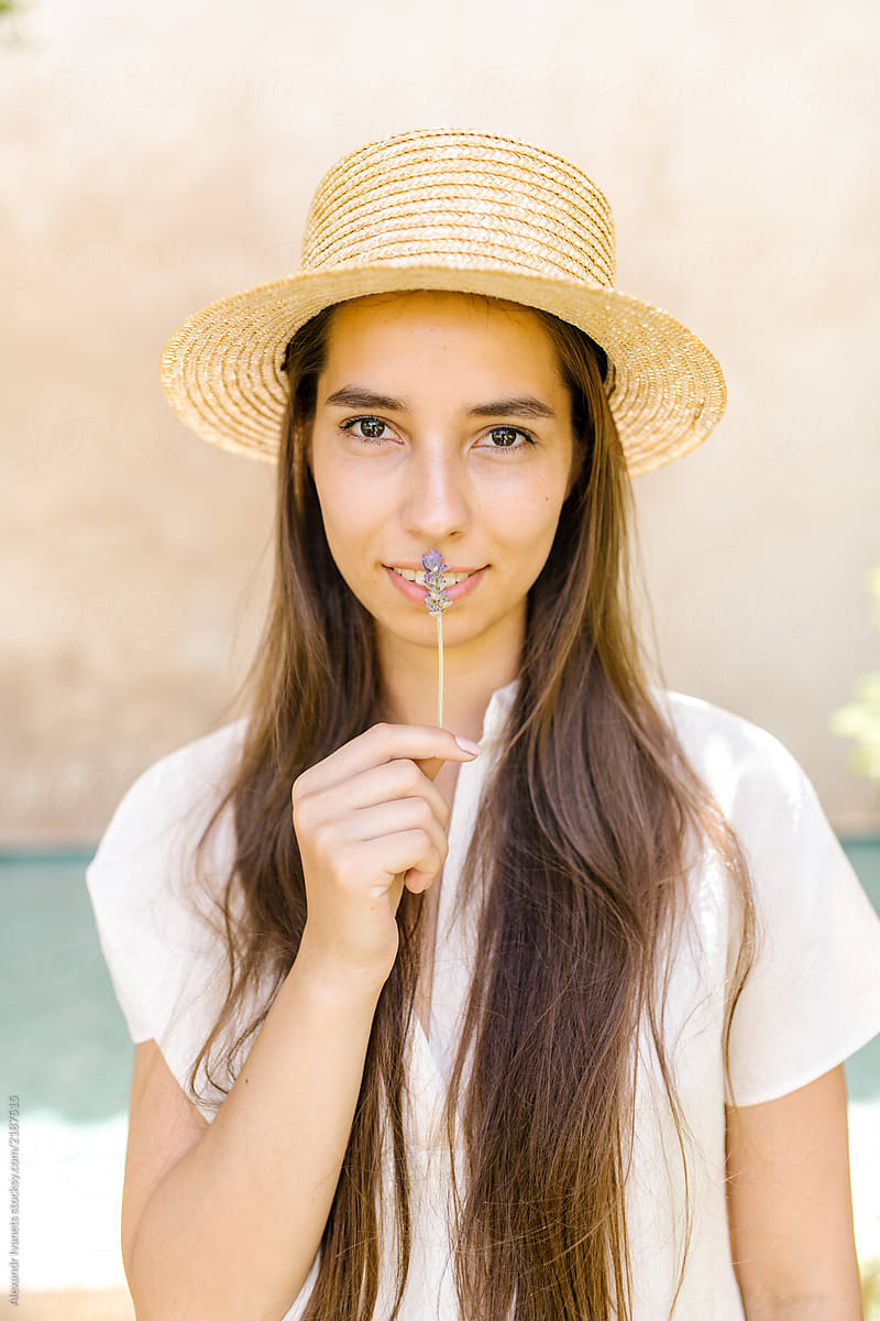 eee6f576 Young brunette in straw hat holding flower. Beautiful young woman in white  ...