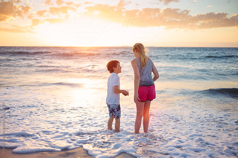 Children in a low wave at the beach at sunset by Angela Lumsden for Stocksy United