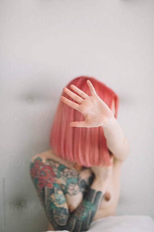 young woman with pink hair hide by Alexey Kuzma for Stocksy United