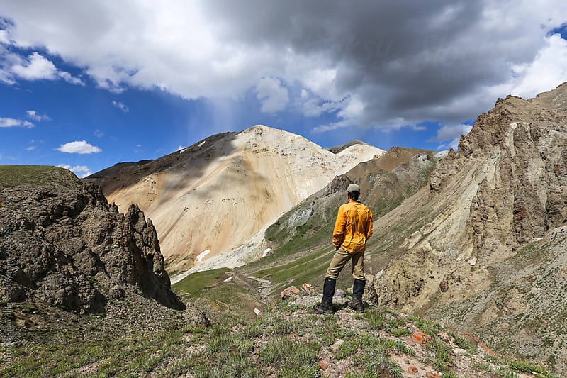 Man looking out over mountains on hike outdoors by Matthew Spaulding for Stocksy United