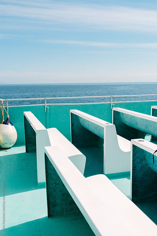 Empty White Benches Sit On Top Of An Aquamarine Sun Deck Of An Alaskan Cruise Ship by Luke Mattson for Stocksy United