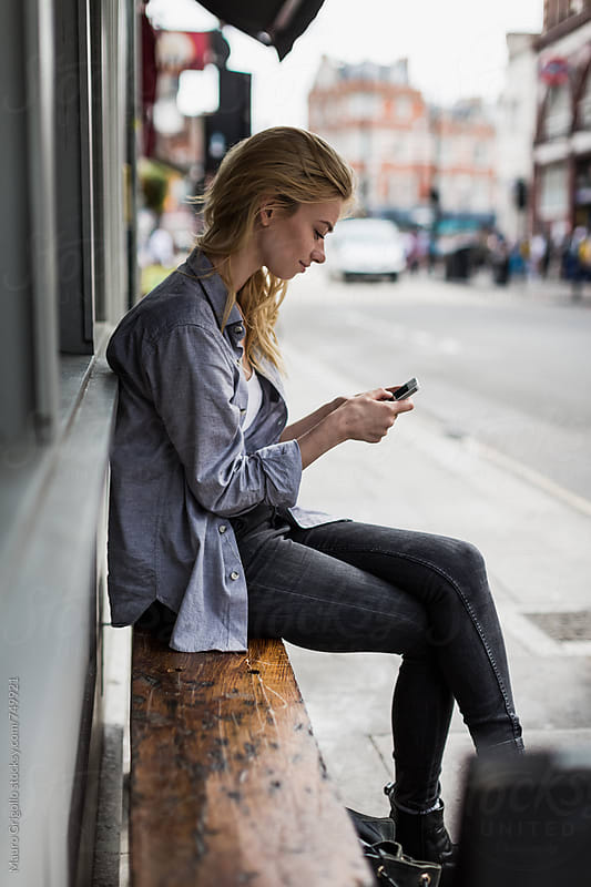 Woman using mobile phone outdoor in the city by Mauro Grigollo for Stocksy United