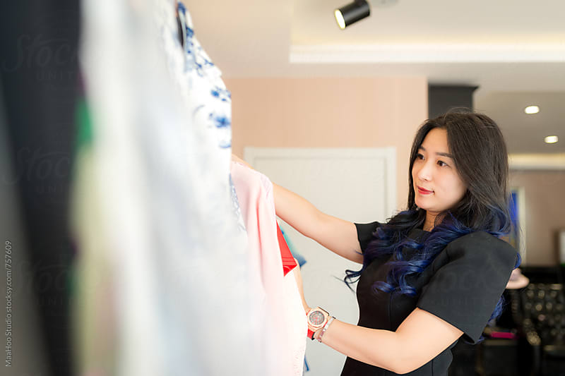 Young clothing store owner arranging dresses by MaaHoo Studio for Stocksy United