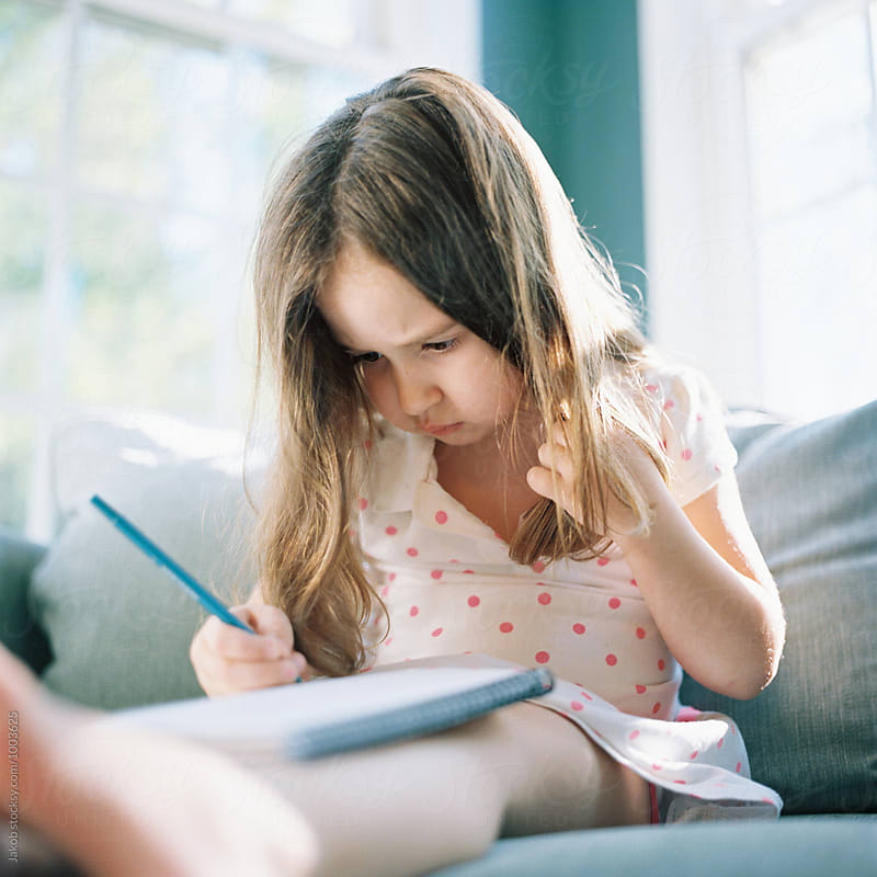 Cute young girl sitting in a a big chair practicing her writing skills by Jakob for Stocksy United