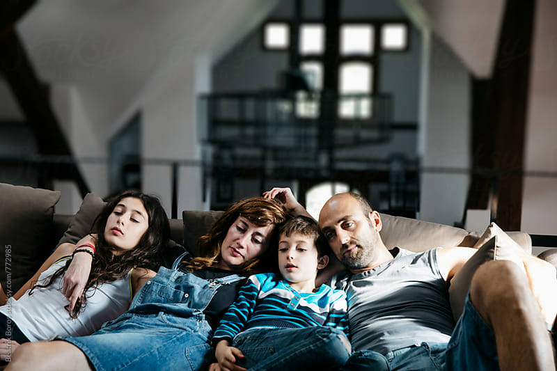 Family with two kids watching tv all together on a lazy weekend day by Beatrix Boros for Stocksy United