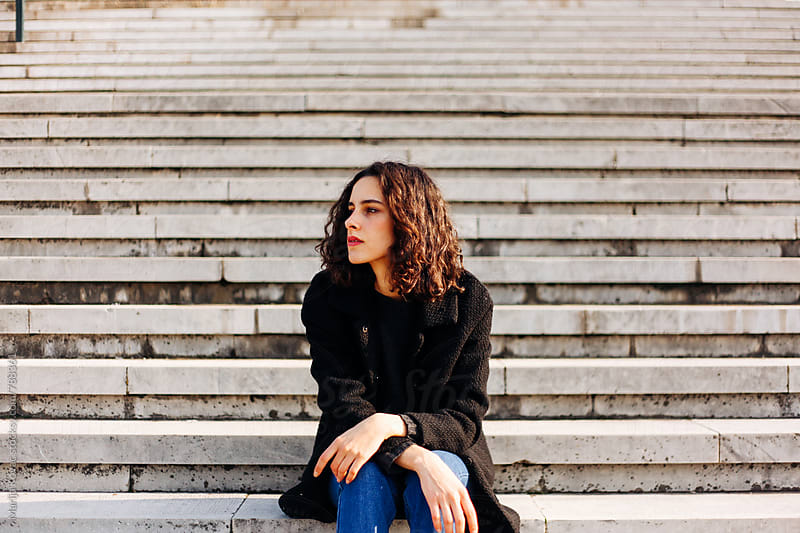 Young woman sitting on the stairs - horizontal by Marija Kovac for Stocksy United